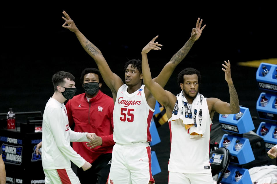 Houston's Brison Gresham (55) and Justin Gorham, right, celebrate from the bench after a score against Rutgers late in the second half of a college basketball game in the second round of the NCAA tournament at Lucas Oil Stadium in Indianapolis Sunday, March 21, 2021. Houston won 63-60. (AP Photo/Mark Humphrey)