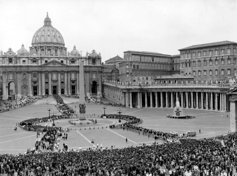 """FILE - This June 5, 1963 file photo shows a general overhead view of St. Peter's Square as a huge crowd moves on continuously into St. Peter's (background) where Pope John XXIII, who died June 3, lies in state. In order to avoid crush and confusion next to the Basilica the crowd is kept on the outskirts of the Square and then let through police cordons and wooden fences across the Square up to the Basilica. Upper right is the Apostolic Palace where the Pontiff died in his apartment on top floor. While much of the focus of Sunday's dual canonization will be on Pope John Paul II's globe-trotting, 26-year papacy and his near-record sprint to sainthood, many older Catholics will be celebrating the short but historic pontificate of the """"Good Pope,"""" John XXIII. (AP Photo/File)"""