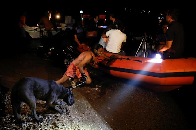 <p>A man holding a dog pushes an inflatable boat as locals are evacuated during a wildfire at the village of Mati, near Athens, Greece, July 23, 2018. (Photo: Alkis Konstantinidis/Reuters) </p>