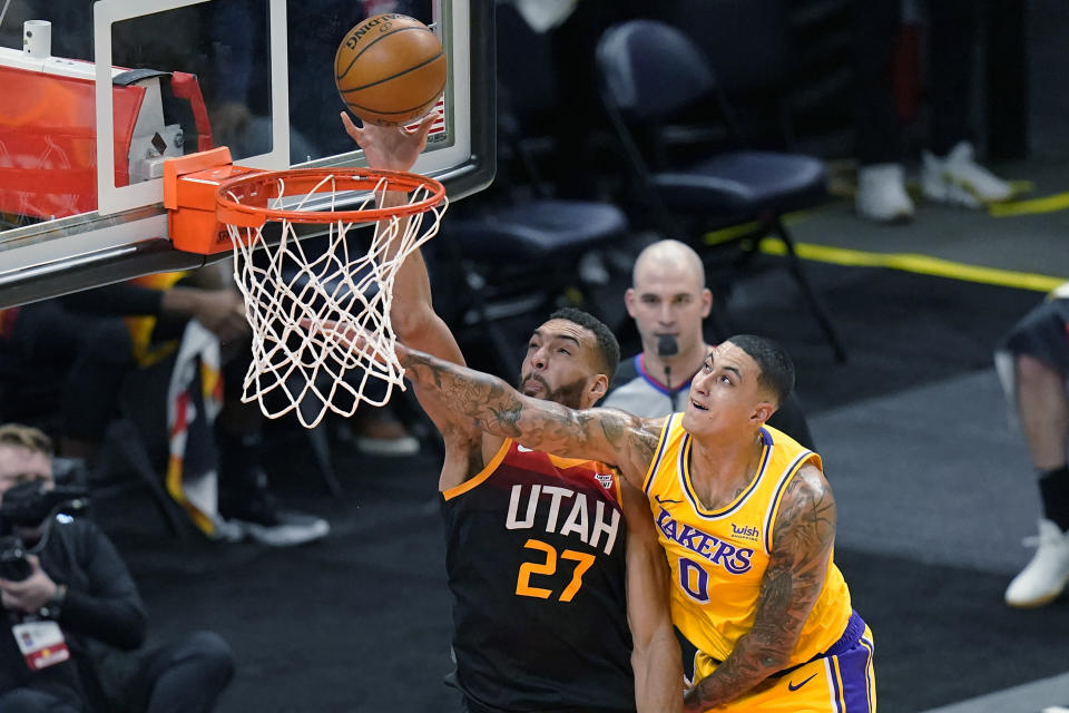 Utah Jazz center Rudy Gobert (27) scores against Los Angeles Lakers forward Kyle Kuzma (0) during the first half of an NBA basketball game Wednesday, Feb. 24, 2021, in Salt Lake City. (AP Photo/Rick Bowmer)