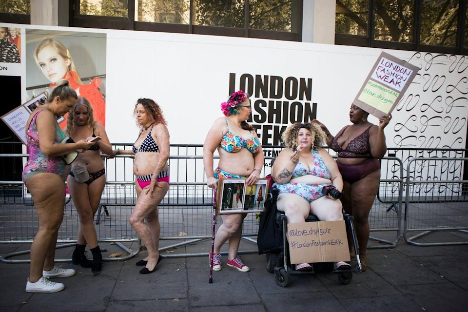 Women with diverse bodies wear bikinis and hold signs that read 'fashion for every body' and 'We want diversity on our runways.'