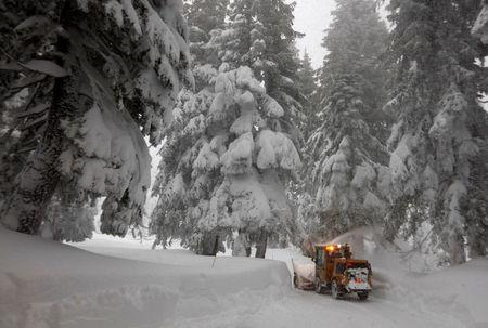 A private contractor clears deep snow from a driveway during a heavy winter storm in Incline Village, Nevada, U.S. January 10, 2017   REUTERS/Bob Strong