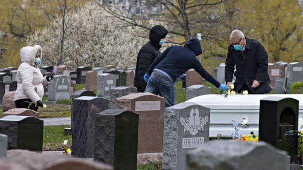PHOTO: Mourners follow social distancing recommendations and wear face masks and gloves while attending a burial in Lawrence, Mass., April 24, 2020. (CJ Gunther/EPA via Shutterstock)