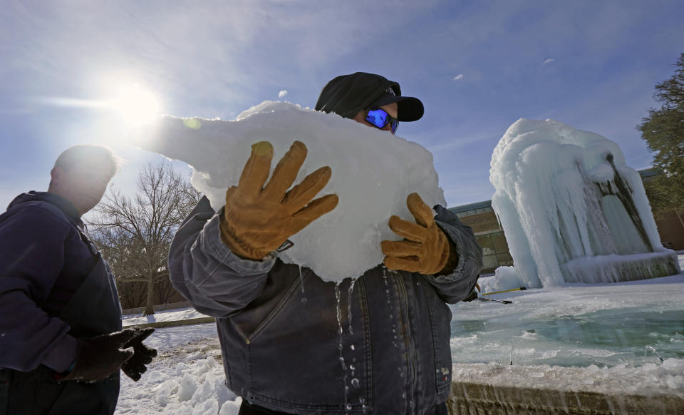 City of Richardson workers clear ice from a frozen fountain Tuesday, Feb. 16, 2021, in Richardson, Texas. Temperatures dropped into the single digits as snow shut down air travel and grocery stores.(AP Photo/LM Otero)