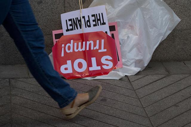<p>A woman walks past a discarded 'Stop Trump' banner as Greenpeace protesters stood in silence outside the U.S. embassy in Madrid, Spain, Friday, June 2, 2017. The protesters gathered at the gates of the United States embassy in the Spanish capital to protest President Donald Trump's decision to pull the world's second-largest carbon dioxide emitter out of the Paris climate agreement. (AP Photo/Paul White) </p>