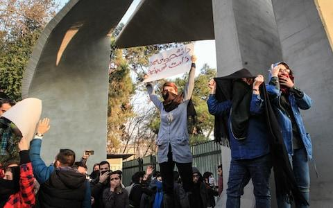 Iranian students protest at the University of Tehran during a demonstration driven by anger over economic problems, in the capital Tehran - Credit: AFP
