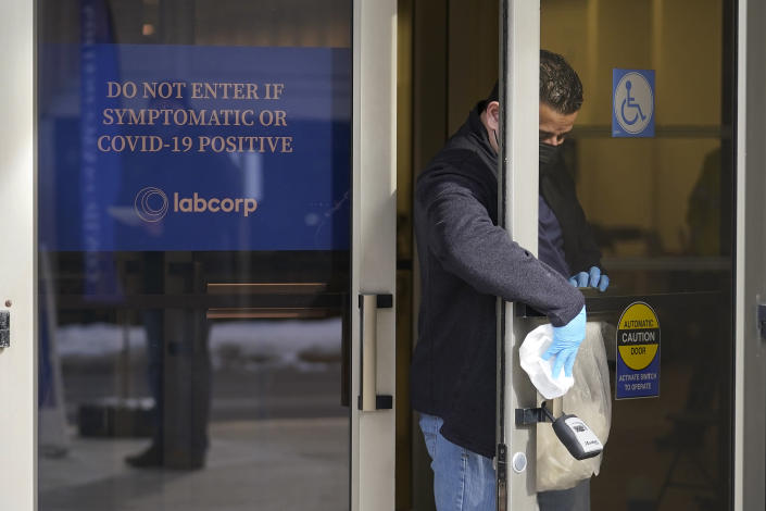 A worker sanitizes a door at an entrance to a COVID-19 vaccination site, Monday, Feb. 22, 2021, in Natick, Mass. (AP Photo/Steven Senne)