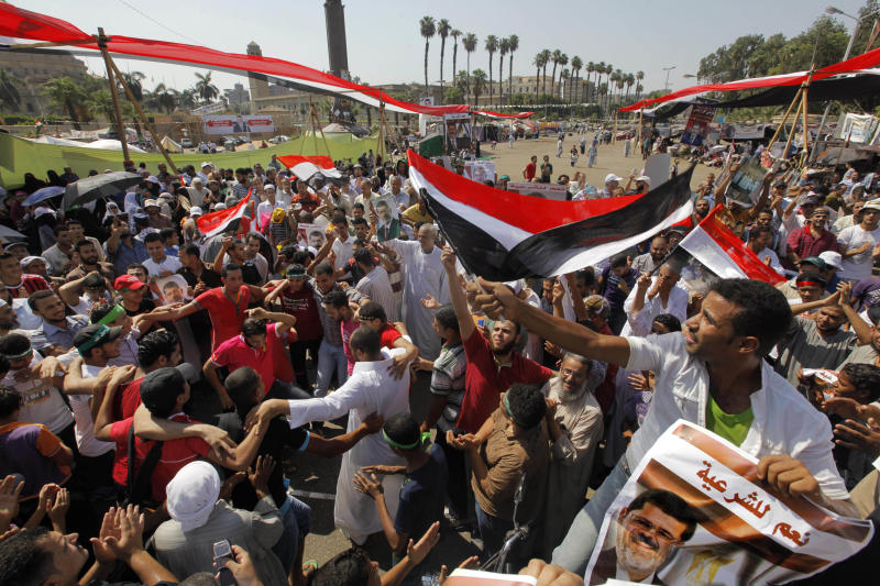 "Supporters of Egypt's ousted President Mohammed Morsi shout slogans and hold his posters during a rally at a camp near Cairo University in Giza, southwest of Cairo, Egypt, Friday, Aug.2, 2013. Arabic reads, ""yes to legitimacy."" An international human rights group has warned of a ""bloodbath"" if Egypt's new leadership uses force to end sit-ins by loyalists of the country's ousted president. The statement by Human Rights Watch came as Mohammed Morsi's followers called for new mass rallies across the country on Friday in defiance of a government order to disband.(AP Photo/Amr Nabil)"
