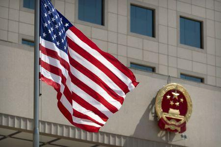 The American flag flies near the national emblem of China outside of the Bayi Building before a welcome ceremony for U.S. Defense Secretary Jim Mattis in Beijing