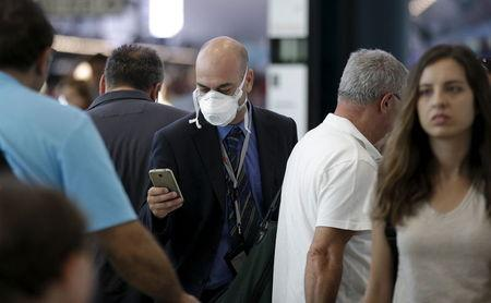 A man wears a mask as he walks at Fiumicino international airport in Rome, Italy, July 13, 2015. REUTERS/Max Rossi