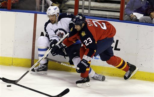 Winnipeg Jets' Blake Wheeler (26) and Florida Panthers' Tyson Strachan (23) fight for the puck during the first period of an NHL hockey game in Sunrise, Fla., Tuesday, March 5, 2013. (AP Photo/J Pat Carter)