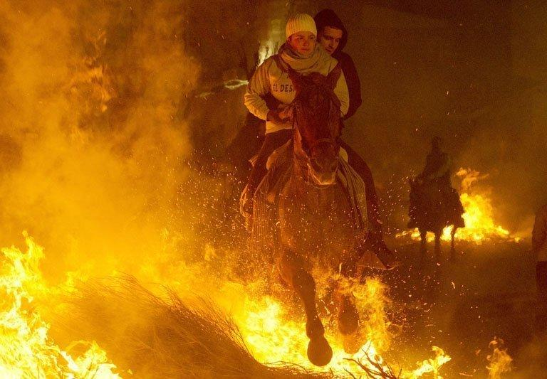 A horsewoman jumps over a bonfire at the Saint Anthony festival in Spain's San Bartolome de Pinares on January 16, 2013