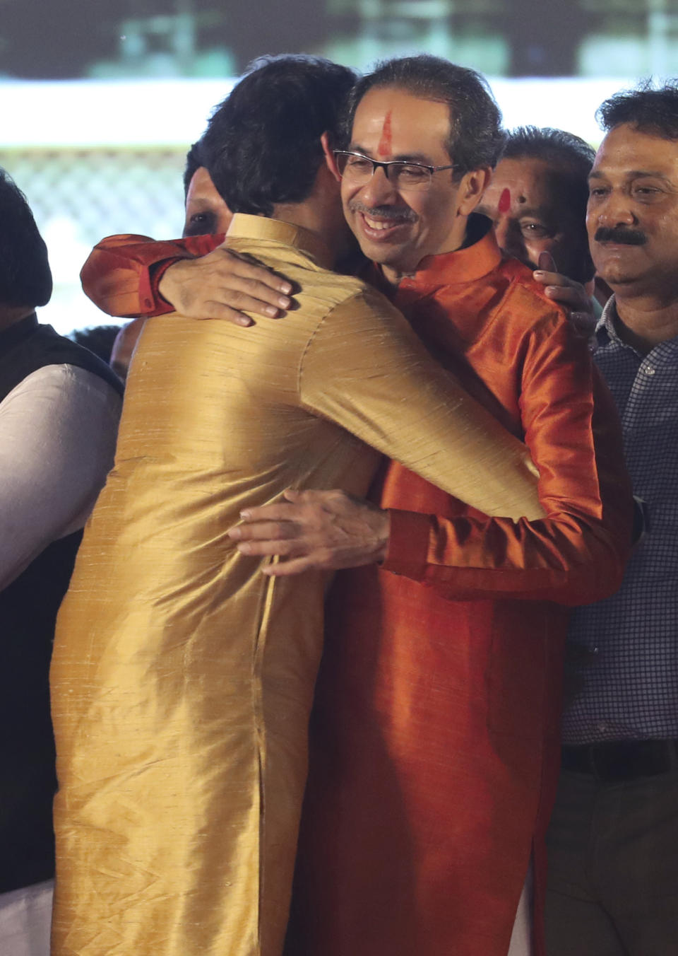 Shiv Sena party leader Uddhav Thackeray, right, is hugged by his son Aaditya Thackeray after he took oath as chief minister of Maharashtra state during a swearing-in-ceremony in Mumbai, Thursday, Nov. 28, 2019. Supporters of the Shiv Sena, Nationalist Congress Party (NCP) and the Congress party thronged Shivaji Park to watch their leaders take oath of office. (AP Photo/Rafiq Maqbool)