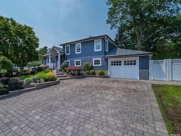 The blue exterior of the house for sale in Long Island with driveway in the foreground and garage door in the background