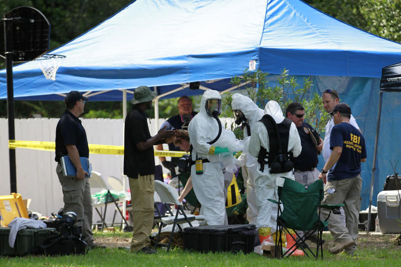 FILE - In this May 31, 2013 file photo, members of an FBI hazardous materials team prepare to enter a residence in New Boston, Texas in connection with a federal investigation surrounding ricin-laced letters mailed to President Barack Obama and New York Mayor Michael Bloomberg. Two U.S. law enforcement officials say Shannon Richardson of New Boston, Texas, has been arrested Friday, June 7, in the investigation. (AP Photo/Texarkana Gazette, Evan Lewis, File) MANDATORY CREDIT