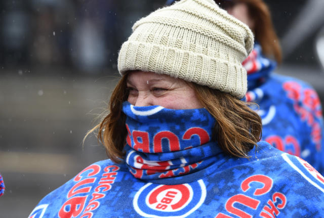 Barb Brauer keeps herself warm outside Wrigley Field after a baseball game between the Atlanta Braves and the Chicago Cubs was postponed on Sunday, April 15, 2018, in Chicago. The game is rescheduled for Monday, May 14, 2018. (AP Photo/Matt Marton)