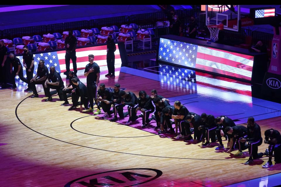 The Boston Celtics team kneels during the playing of the national anthem before their game against the Miami Heat, who also kneeled, on Jan. 6, 2021. (AP Photo/Marta Lavandier)