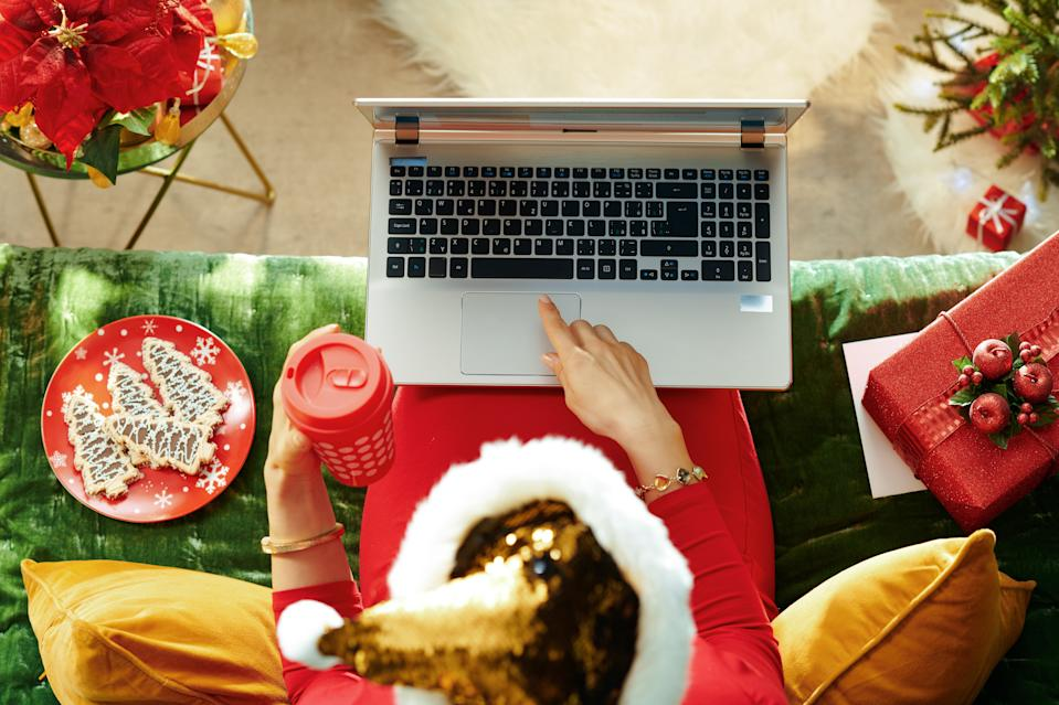 Holiday season. Upper view of young housewife in sparkle gold sequin santa hat with cup of coffee reading on a laptop while sitting on couch in the modern living room at Christmas.