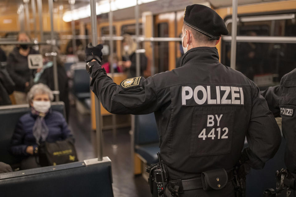 Police officers and an employee of VAG (Verkehrs-Aktiengesellschaft Nuernberg) in a subway train to control the mask requirement, to avoid the spread of the coronavirus, on the public transport service in Nuernberg, Germany, Friday, Oct. 23, 2020. (Daniel Karmann/dpa via AP)
