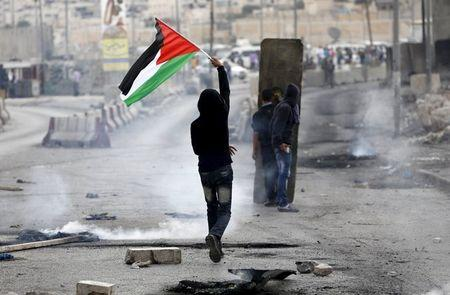 Palestinian protester holds a Palestinian flag as others take cover during clashes with the Israeli army at Qalandia checkpoint near occupied West Bank city of Ramallah