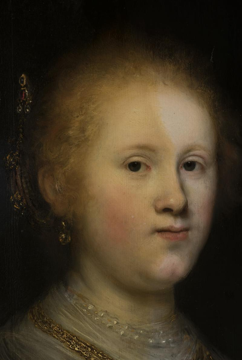 A photograph of the portrait mid-restoration shows the extent of the layers of varnish (left side) and what the work looked like when it was first painted (right side).