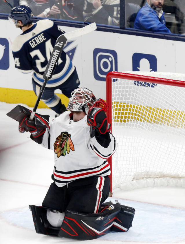Chicago Blackhawks goalie Robin Lehner, bottom, of Sweden, reacts after stopping a shot by Columbus Blue Jackets forward Nathan Gerbe to win an NHL hockey game in an overtime period in Columbus, Ohio, Sunday, Dec. 29, 2019. (AP Photo/Paul Vernon)
