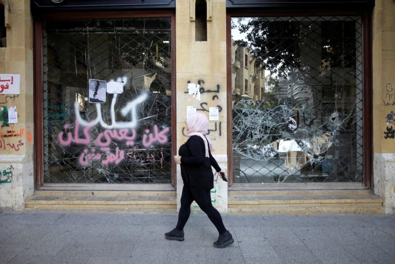 A woman walks past a closed bank office in Beirut