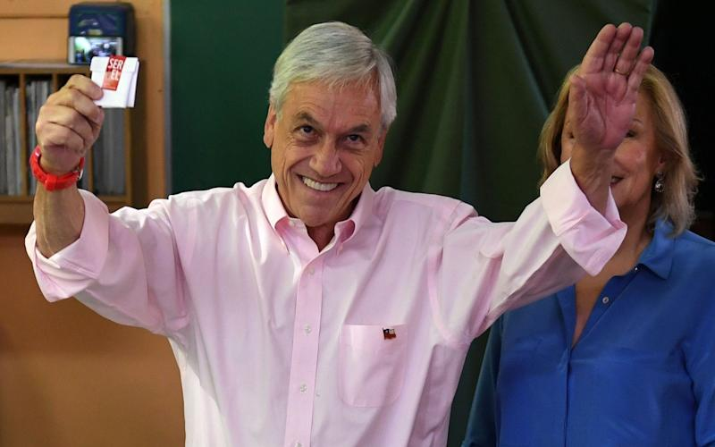 Sebastian Pinera, pictured casting his vote earlier in the day, won the election - AFP