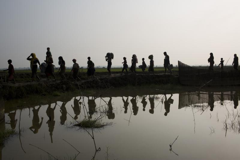 """-FILE- In this Tuesday, Sept. 5, 2017, file photo members of Myanmar's Rohingya ethnic minority walk through rice fields after crossing the border into Bangladesh near Cox's Bazar's Teknaf area. Gambia has filed a case at the United Nations' highest court in The Hague, Netherlands, Monday, Nov. 11, 2019, accusing Myanmar of genocide in its campaign against the Rohingya Muslim minority. A statement released Monday by lawyers for Gambia says the case also asks the International Court of Justice to order measures """"to stop Myanmar's genocidal conduct immediately."""" (AP Photo/Bernat Armangue, file)"""