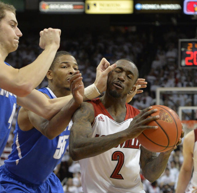 Louisville's Russ Smith, right, is trapped by Memphis' Austin Nichols, left, and Geron Johnson during the second half of an NCAA college basketball game on Thursday Jan. 9, 2014, in Louisville, Ky. Memphis defeated Louisville 73-67. (AP Photo/Timothy D. Easley)