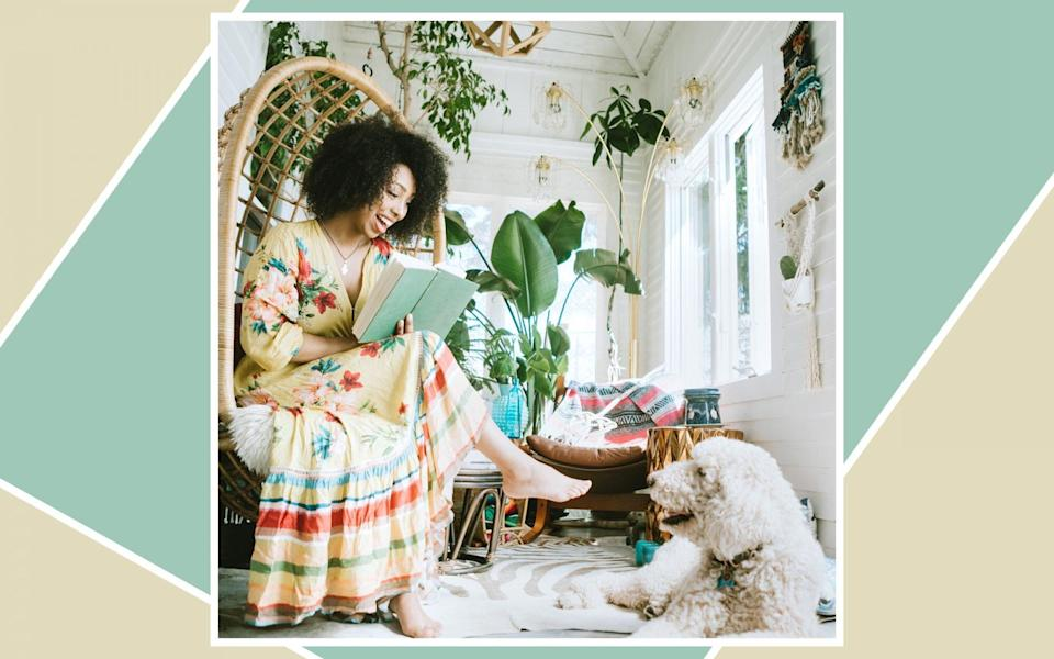 Woman sitting in her living room, reading a book with her dog