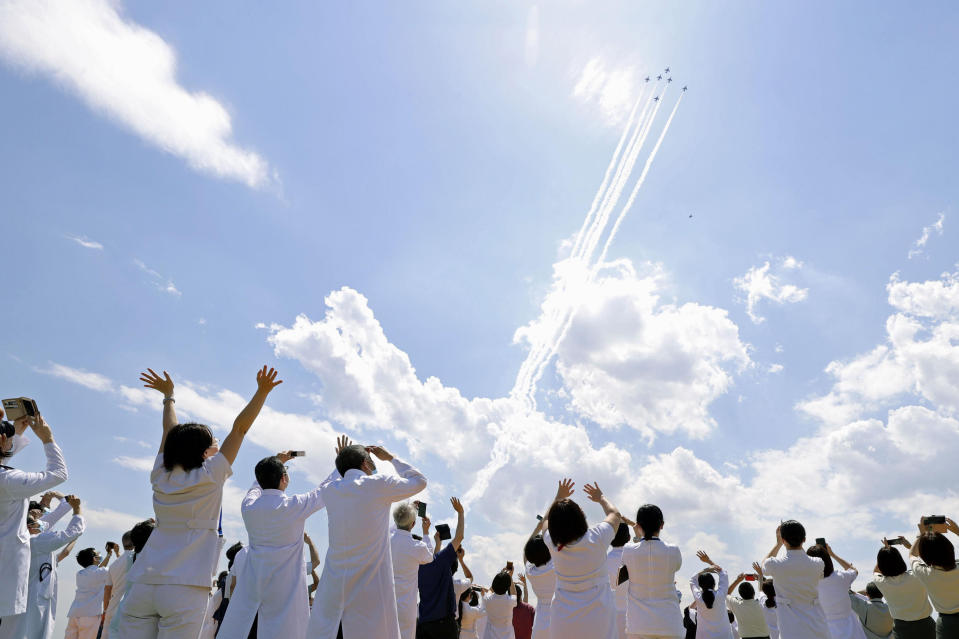 Blue Impulse of the Japan Air Self-Defense Force fly over medical workers of Self-Defense Forces Central Hospital in Tokyo, Friday, May 29, 2020, in Tokyo. A Japanese Air Self-Defense Force's aerobatics team performed a demonstration flight to express support and gratitude for medical workers. The six Blue Impulse aircraft flew for about 20 minutes over Tokyo to thank for doctors, nurses and other medical staff. (Kyodo News via AP)