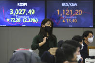 A currency trader walks near screens showing the Korea Composite Stock Price Index (KOSPI), left, and the foreign exchange rate between U.S. dollar and South Korean won at the foreign exchange dealing room of the KEB Hana Bank headquarters in Seoul, South Korea, Friday, Feb. 26, 2021. Asian shares skidded Friday after rising bond yields triggered a broad sell-off on Wall Street that erased the markets gain for the week and handed the Nasdaq composite index its steepest loss since October. (AP Photo/Ahn Young-joon)