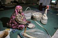 Halima Mohamed, a resident who returned to the Libyan city of Tawergha, sits making traditional palm products