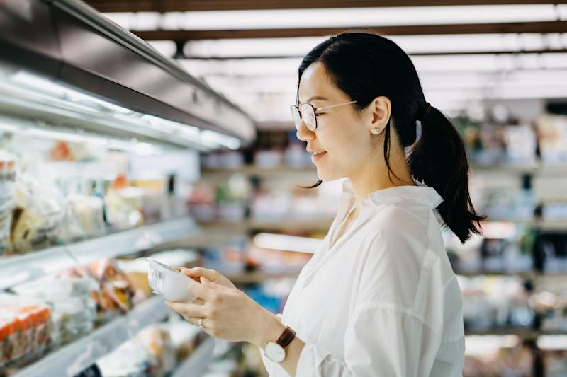 Young Asian woman grocery shopping in supermarket and reading nutrition label on a packet of fresh egg