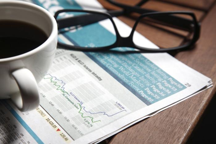 Glasses and a coffee on top of a financial newspaper.