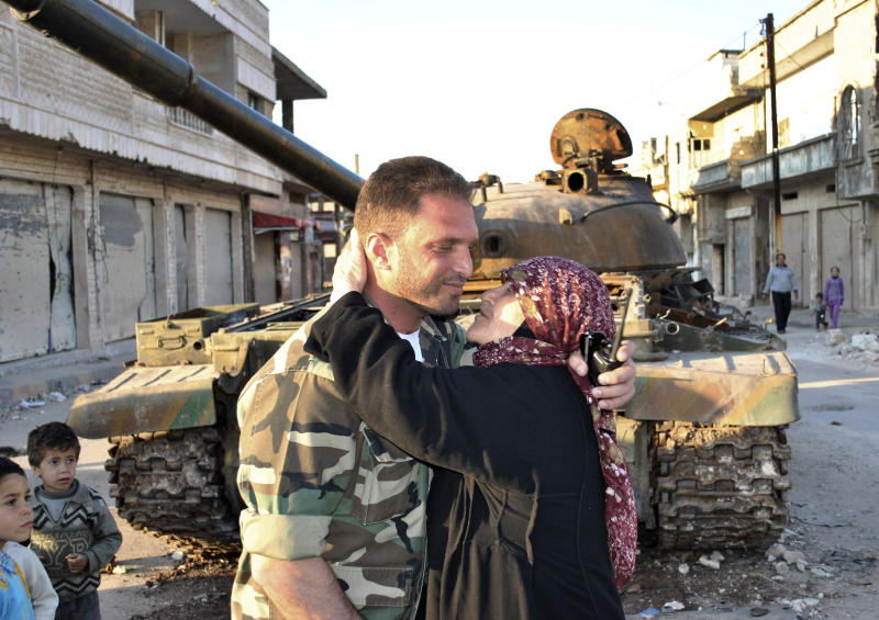 In this Wednesday, March 21, 2012 file photo, a Syrian woman, right, kisses a soldier from the Free Syrian Army, in front a destroyed Syrian army forces tank which was attacked during clashes between the Syrian government forces and the Syrian rebels in Rastan, Syria. As Syria's rebels gain ground across the country, the fighters are trying to win the hearts and minds of their countrymen and the international community --capturing army diesel trucks to give to impoverished villagers, working to restore damaged power lines and smuggling in foreign journalists. (AP Photo, File)