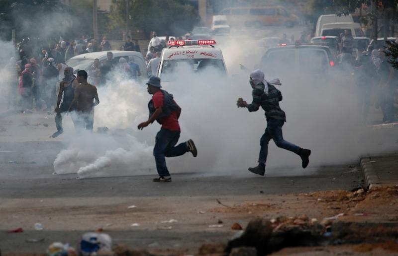 Palestinian protesters run through tear gas in clashes with Israeli security forces in Beit El, near the West Bank city of Ramallah, on October 10, 2015 (AFP Photo/Abbas Momani)