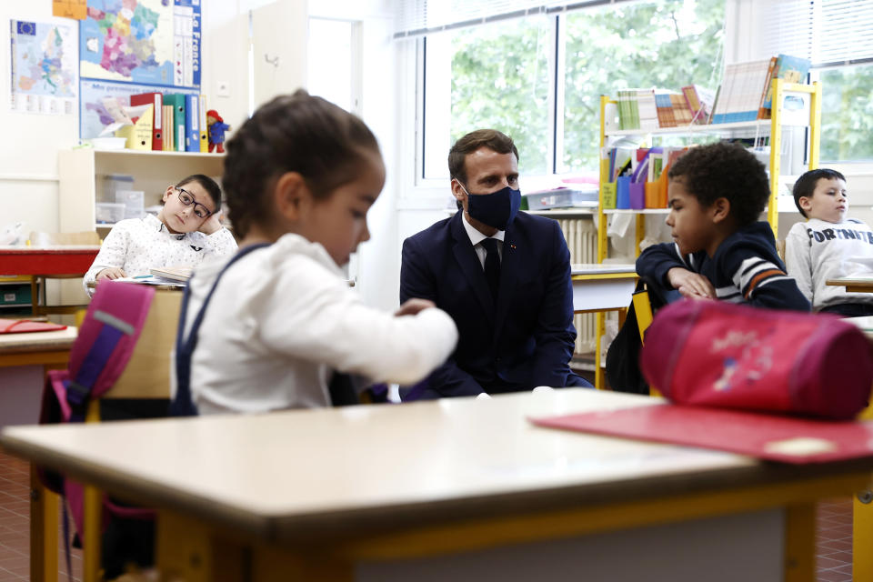 French President Emmanuel Macron, wearing a protective face mask, speaks with schoolchildren during a class at the Pierre Ronsard elementary school Tuesday, May 5 2020 in Poissy, outside Paris. Starting from May 11, all French businesses will be allowed to resume activity and schools will start gradually reopening. (Ian Langsdon, Pool via AP)