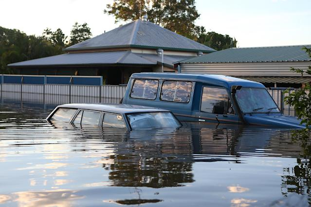BUNDABERG, AUSTRALIA - JANUARY 29: Cars float in a flooded street as parts of southern Queensland experiences record flooding in the wake of Tropical Cyclone Oswald on January 29, 2013 in Bundaberg, Australia.Four deaths have been confirmed and thousands have been evacuated in Bundaberg as the city faces it's worst flood disaster in history. Rescue and evacuation missions continue today as emergency services prepare to move patients from Bundaberg Hospital to Brisbane amid fears the hospital could lose power. (Photo by Chris Hyde/Getty Images)