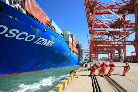Workers help to dock a China Ocean Shipping Company (COSCO) container ship at a port in Qingdao