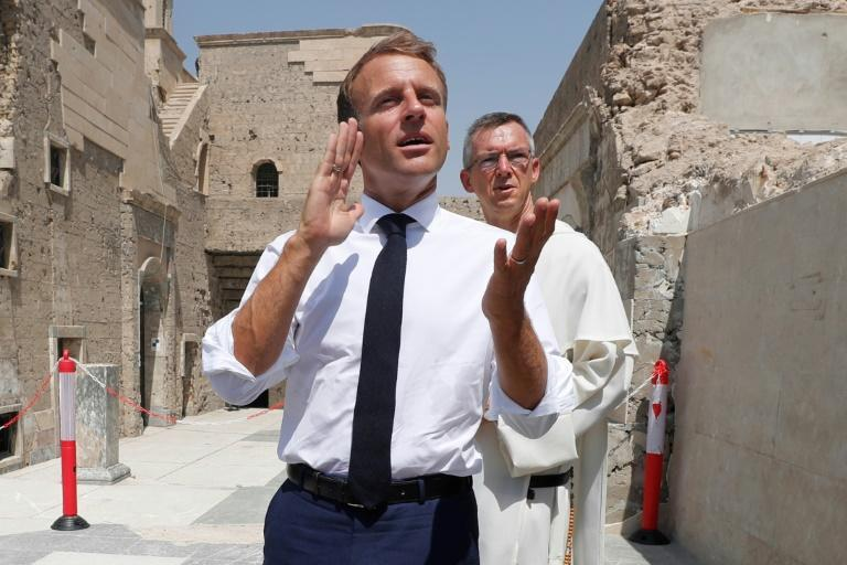 French President Emmanuel Macron speaks to journalists at the Our Lady of the Hour Church in Mosul, with Dominican Father Olivier Poquillon (AFP/Ahmad AL-RUBAYE)