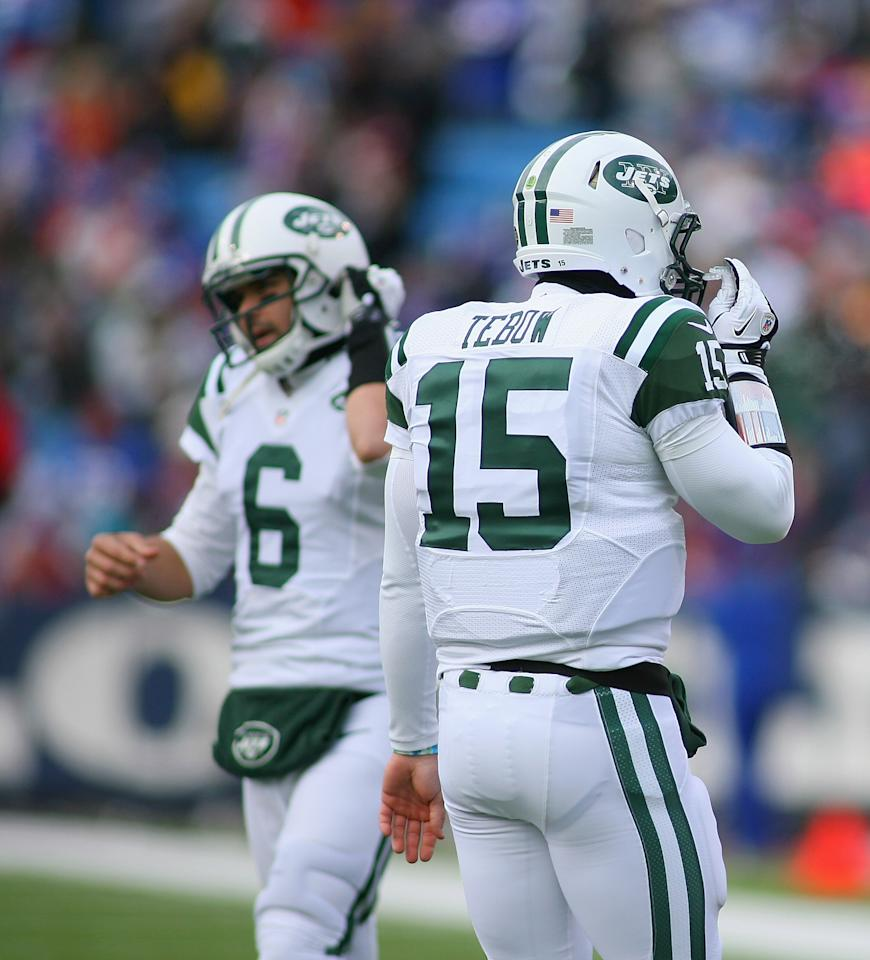 ORCHARD PARK, NY - DECEMBER 30:  Tim Tebow #15 of the New York Jets walks off the field as Mark Sanchez #6 walks on against the Buffalo Bills at Ralph Wilson Stadium on December 30, 2012 in Orchard Park, New York.  (Photo by Rick Stewart/Getty Images)