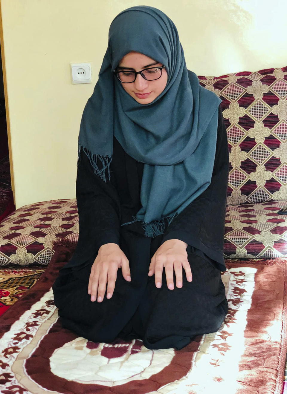 Salgy Baran, 18, who received the highest the highest score in the entire country on Afghanistan's university entrance exams this year, prays inside her home in Kabul, Afghanistan, Thursday, Aug. 26, 2021. Baran wants to stay in the country and become a doctor. But as with so many other Afghans, those plans were thrown into doubt when the Taliban rolled into the capital of Kabul earlier this month. (AP Photo/Nillab Burhan)