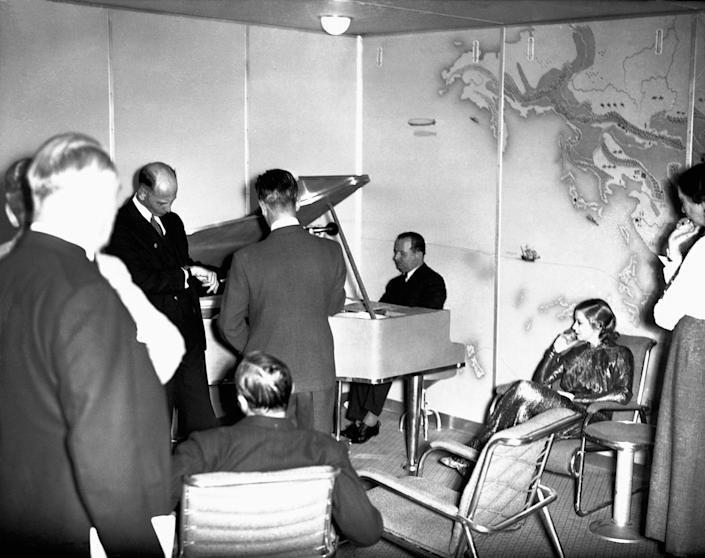 <p>Passengers gather around the piano in the lounge of the Hindenburg. (Corbis via Getty Images) </p>