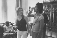 <p>Freddie Mercury drinking a class of champagne as Mary Austin, his ex-girlfriend, looks on during party for friends at home in 1977.</p>
