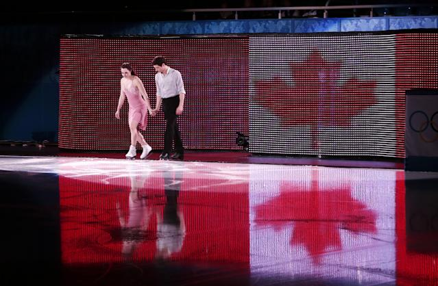 Tessa Virtue and Scott Moir of Canada step onto the ice before their performance for the figure skating exhibition gala at the Iceberg Skating Palace during the 2014 Winter Olympics, Saturday, Feb. 22, 2014, in Sochi, Russia. (AP Photo/Ivan Sekretarev)