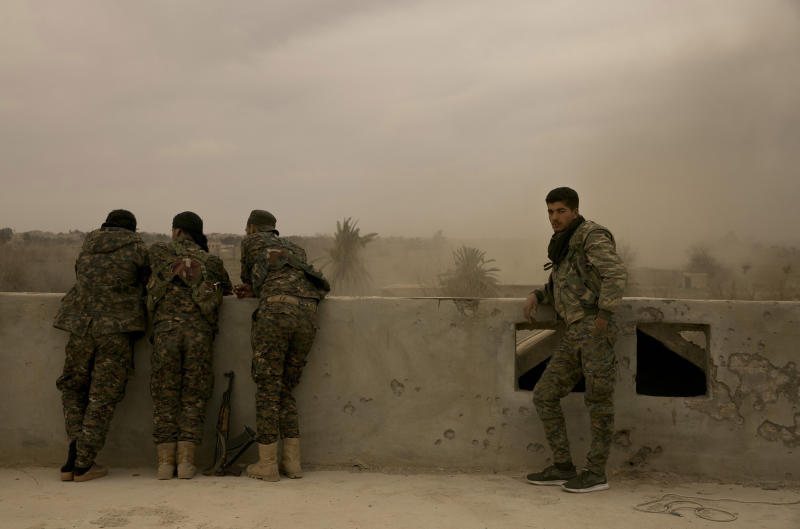 U.S.-backed Syrian Democratic Forces (SDF) soldiers watch from a rooftop the battle to oust Islamic State militants from Baghouz, Syria, Wednesday, March 13, 2019. (AP Photo/Maya Alleruzzo)