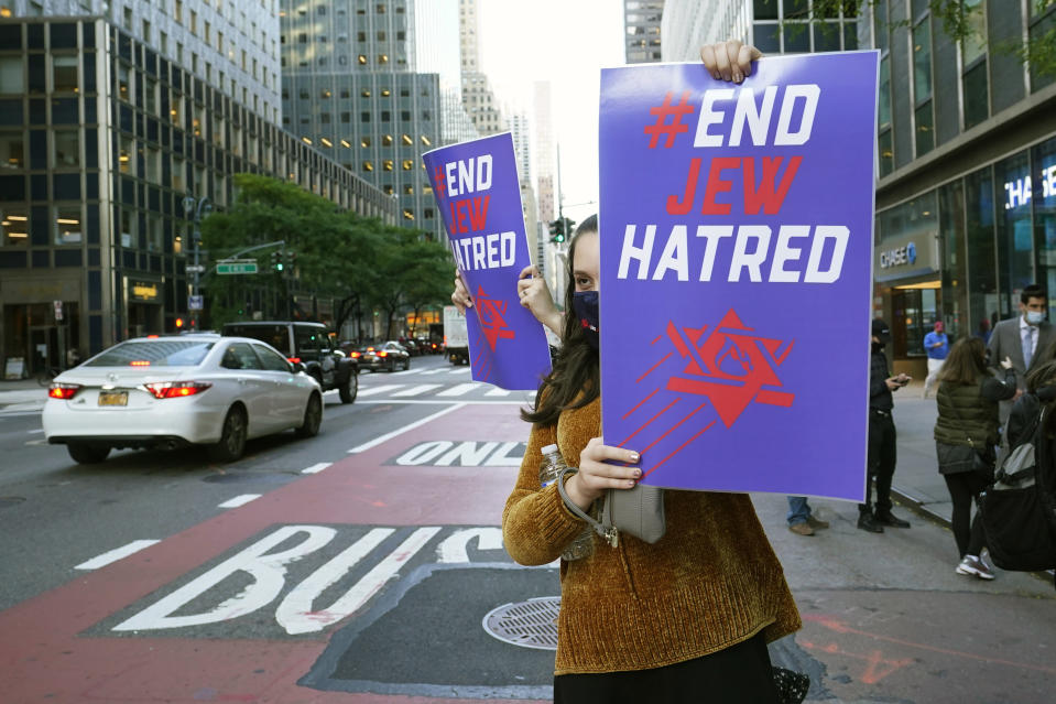 A young woman holds a sign toward oncoming traffic on Third Avenue outside the offices of New York Gov. Andrew Cuomo, Thursday, Oct. 15, 2020, in New York. Some members of the Jewish community are angered at Cuomo's recent move ordering schools to close in Orthodox Jewish communities in Brooklyn and north of New York City where coronavirus cases are trending upward. Three Rockland County Jewish congregations filed a lawsuit Wednesday accusing Cuomo of engaging in a streak of anti-Semitic discrimination with a crackdown on religious gatherings. (AP Photo/Kathy Willens)