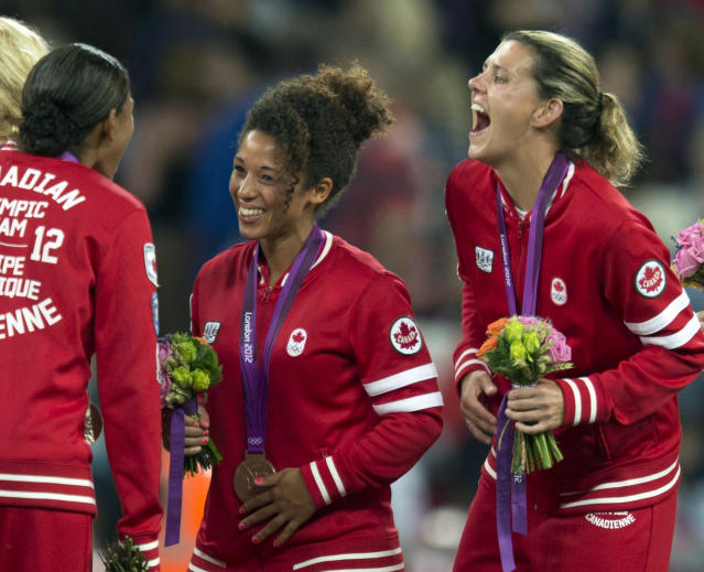 Canada women's soccer players Robyn Gayle (left), Desiree Scott and Christine Sinclair (right) share a laugh after being presented with their Bronze medals at the Olympic Games in London on Thursday August 9, 2012. THE CANADIAN PRESS/Frank Gunn